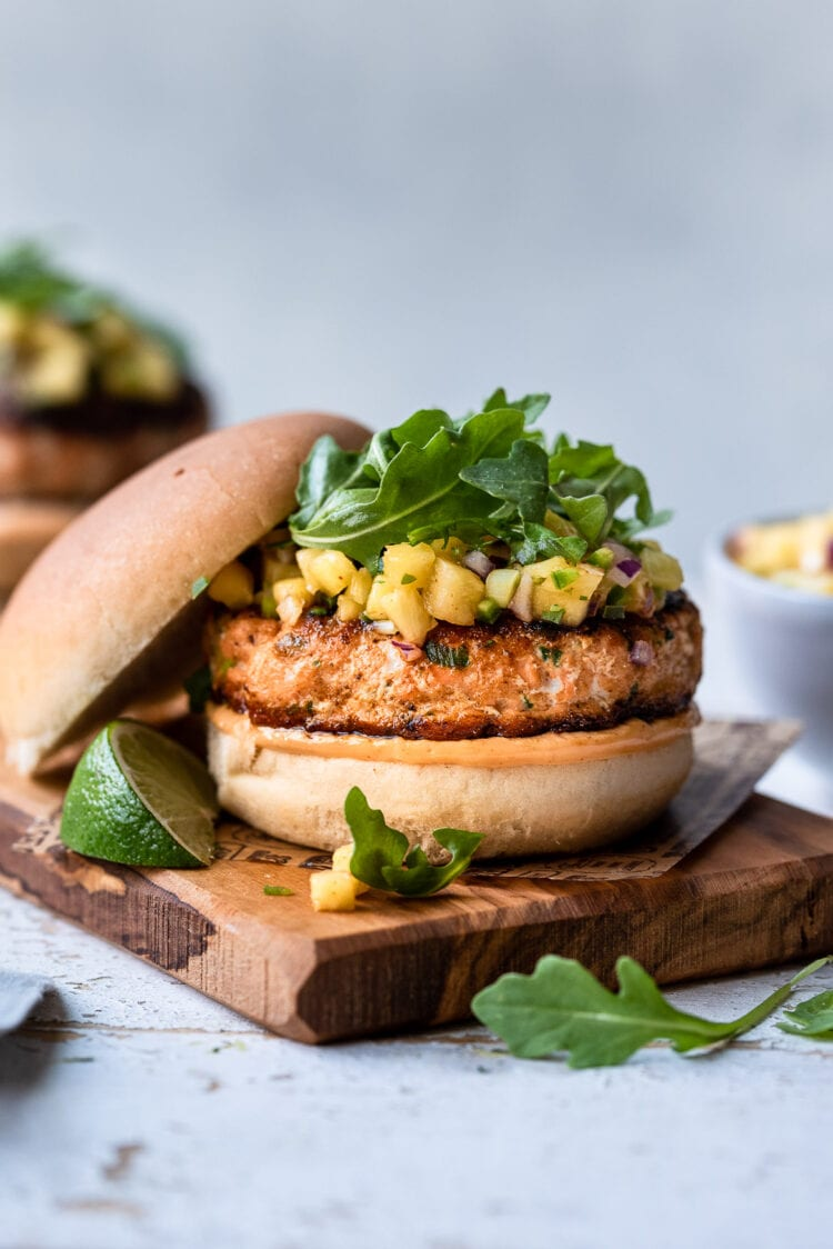 Thai Salmon Burgers topped with pineapple salsa and arugula.