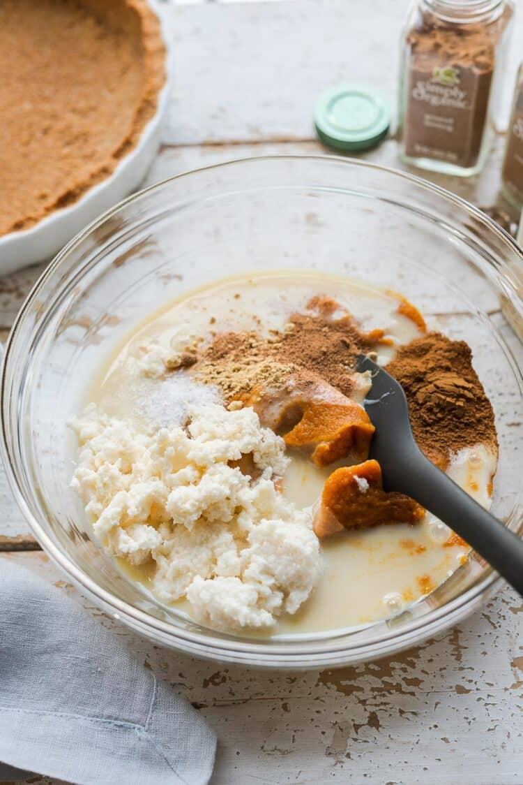 Ingredients for cassava pumpkin pie in a glass bowl.