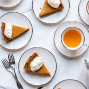 Slices of Cassava Pumpkin Pie and whipped cream on white plates with cups of tea.