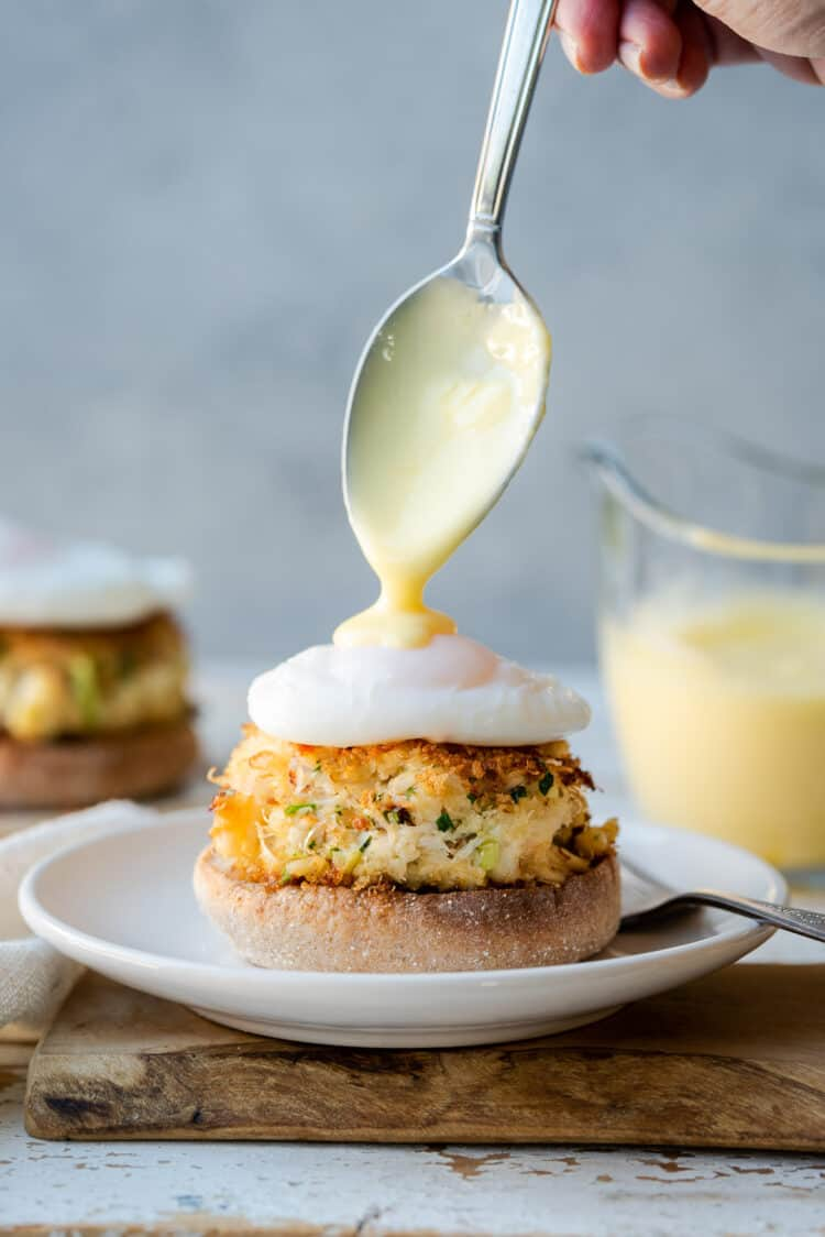 Drizzling hollandaise sauce over a crab cake Benedict.
