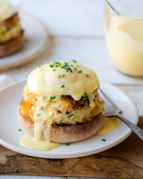 Crab Cake Benedict on white plate with hollandaise sauce.