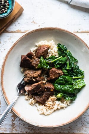Filipino Pork Adobo served over rice with a side of sautéed kale in a bowl.