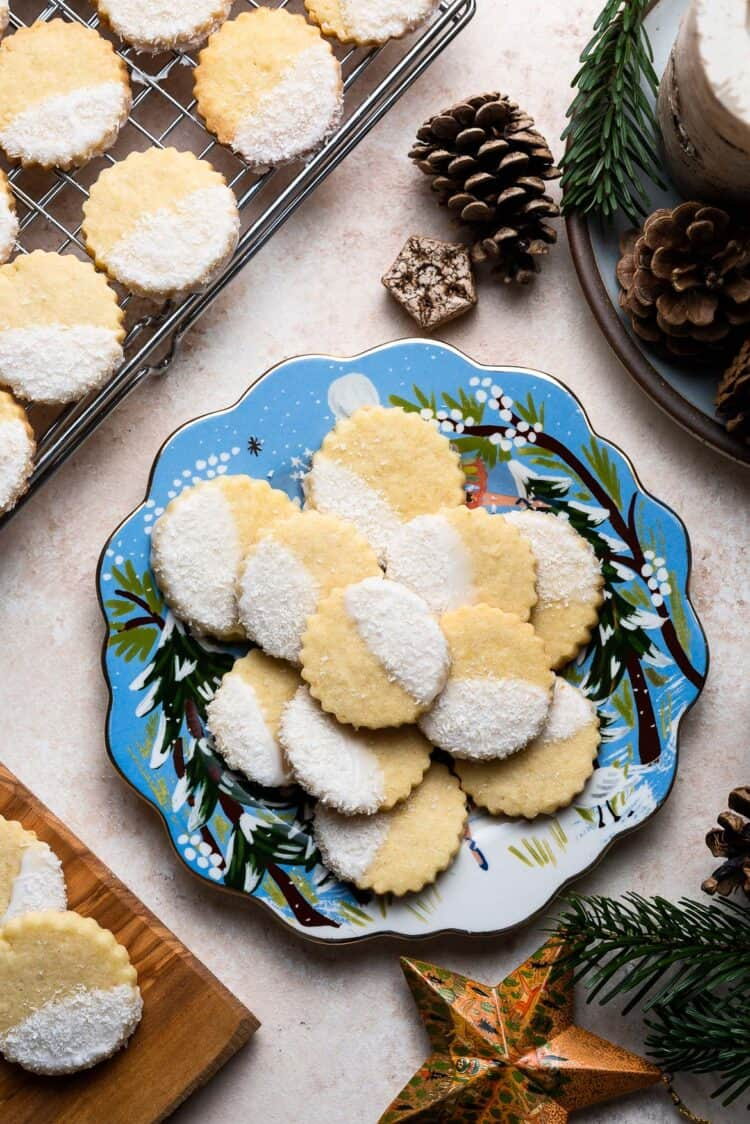 Blue holiday plate of Coconut Shortbread Cookies with coconut glaze and shredded coconut with pine cones in the background.