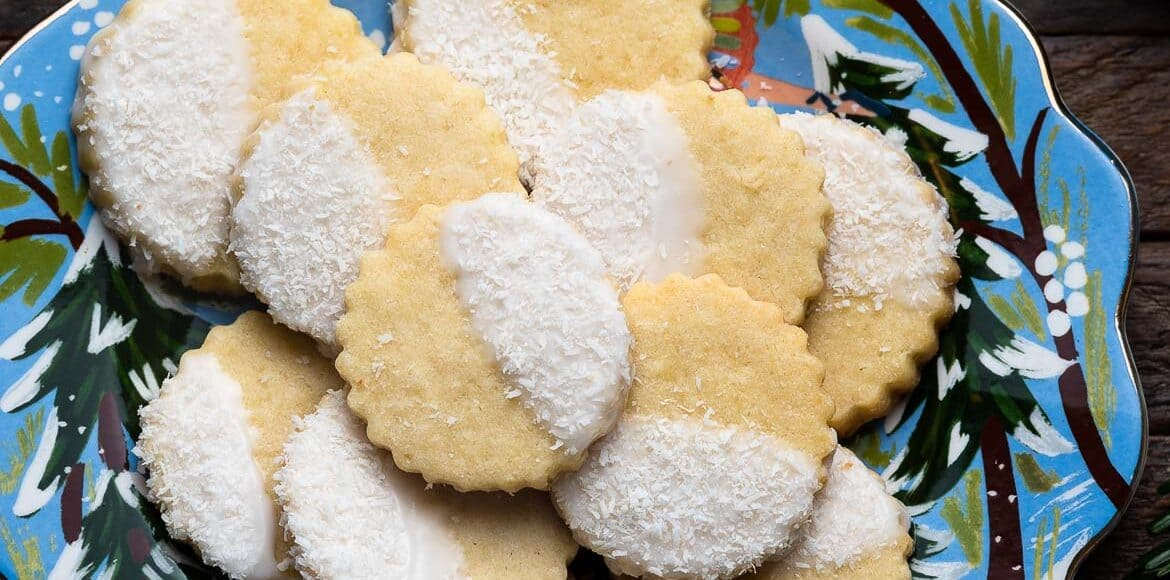 Holiday plate of Coconut Shortbread Cookies with coconut glaze and shredded coconut.