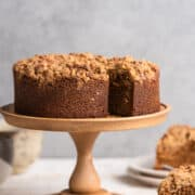 Spanish Coffee Cake on a wood cake stand with slices on the side.