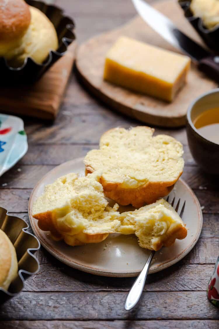 Ensaymada (Filipino brioche bread) on a cream plate cut in half.