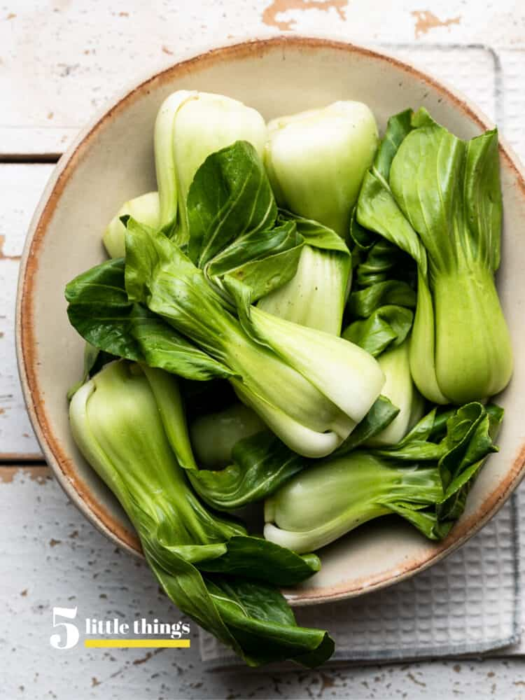 Baby bok choy in a cream bowl.