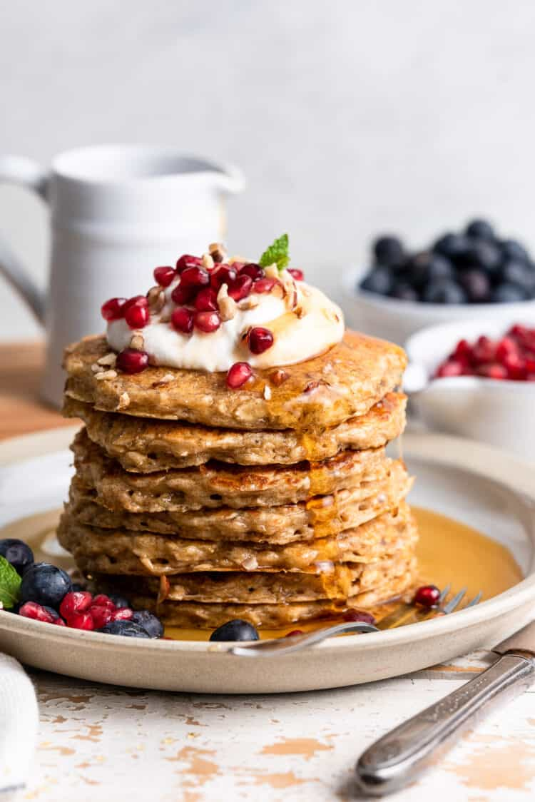 Stack of oatmeal pancakes topped with coconut whipped cream, pomegranate seeds and crushed hazelnuts, and served with maple syrup and blueberries.