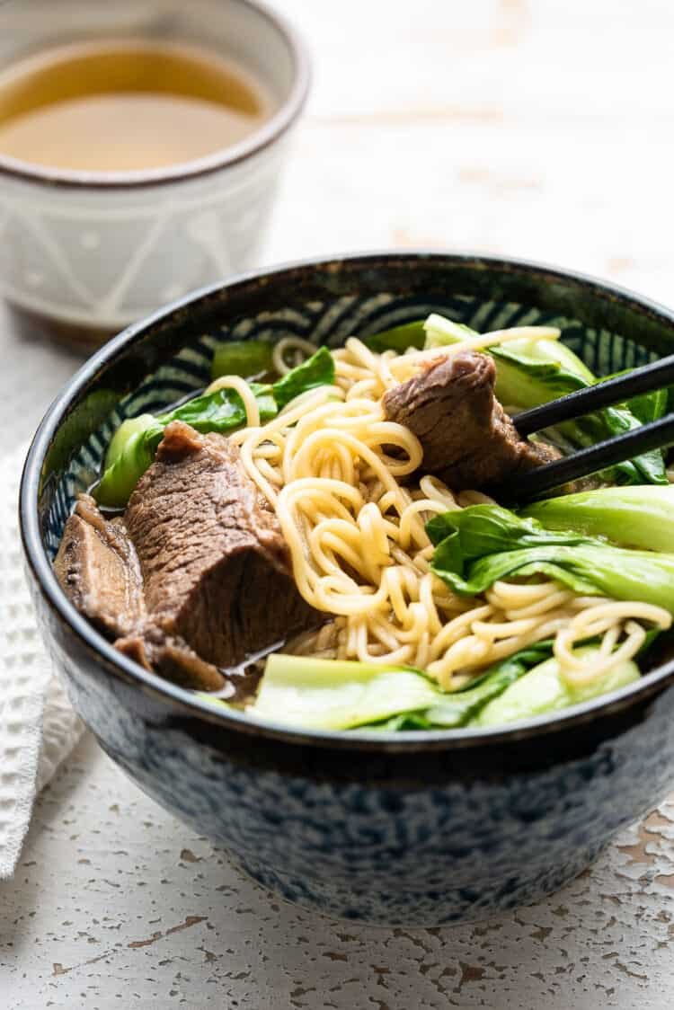Instant Pot Short Rib Ramen in a blue and black ramen bowl, with chopsticks picking up short rib.