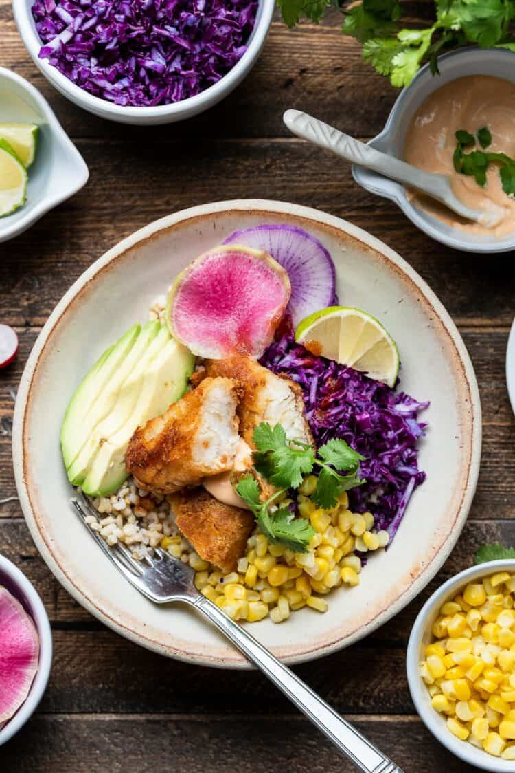 Spicy fish taco bowl with cabbage slaw in a cream bowl on a wooden table with toppings on the side.