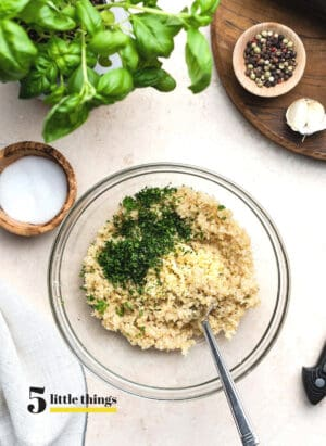 Quinoa with parsley in a clear mixing bowl.