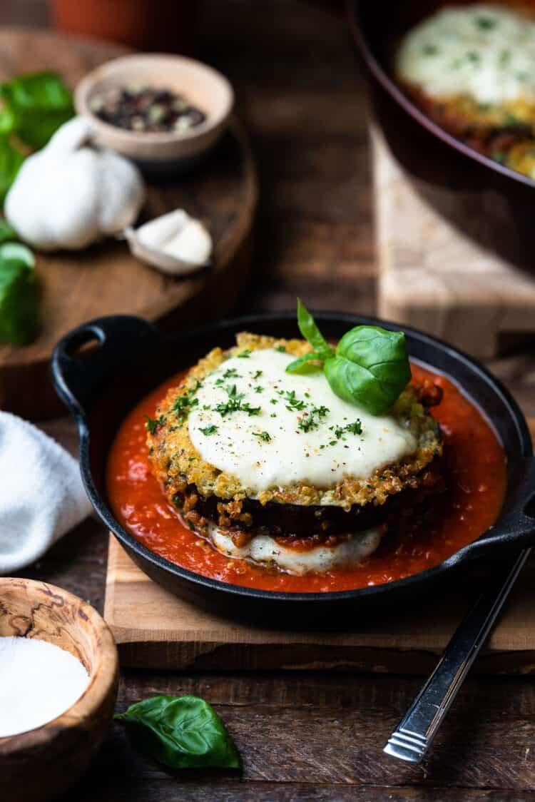 Quinoa Crusted Eggplant Parmigiana in a black dish.