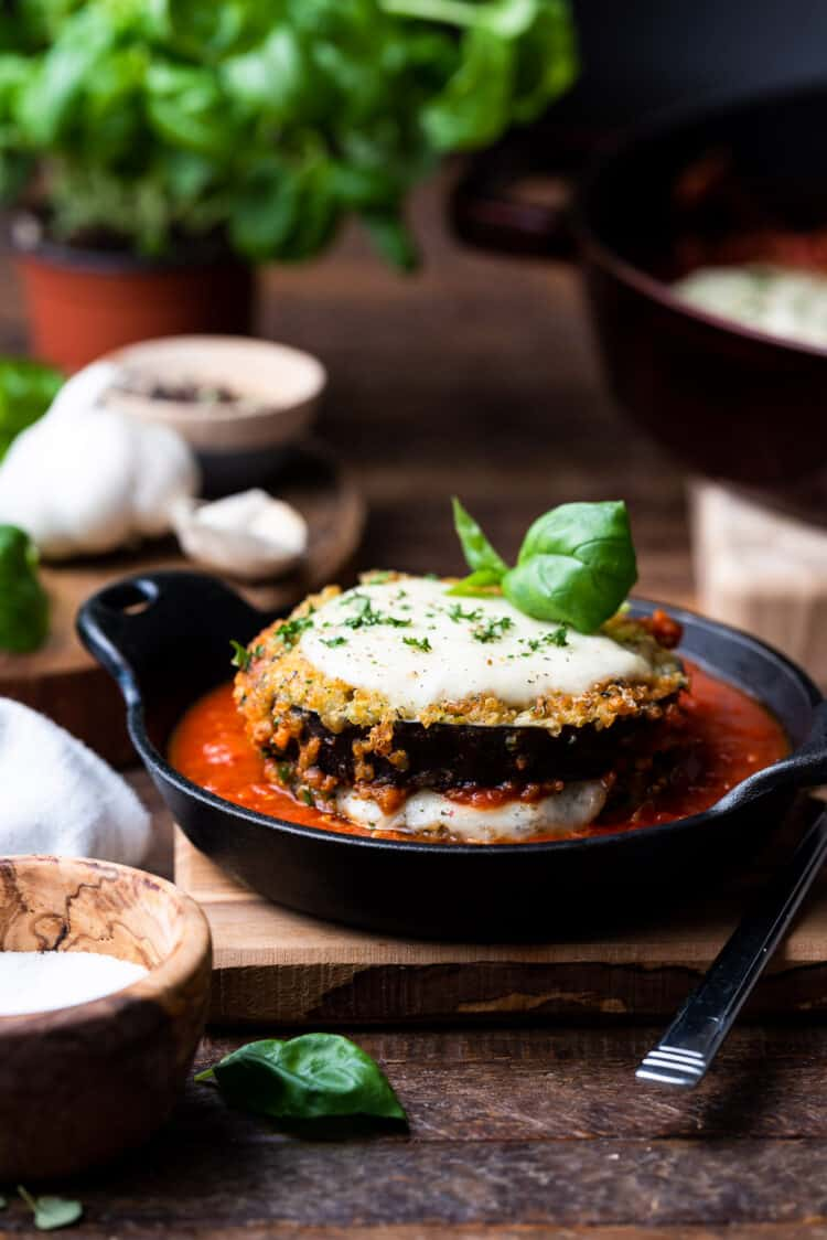 Quinoa crusted eggplant parmesan stacked in a black dish with marinara sauce.