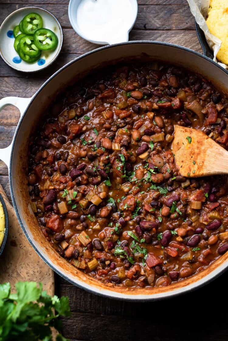 A pot of vegan chili made with beans and mushrooms with a wooden spoon and garnishes on the side.