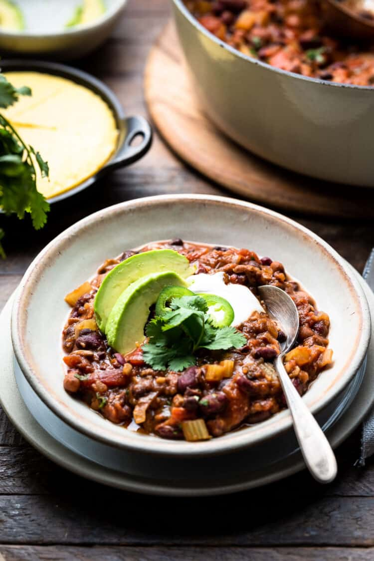A bowl of vegan chili with beans, avocado and cilantro and a side of corn bread.