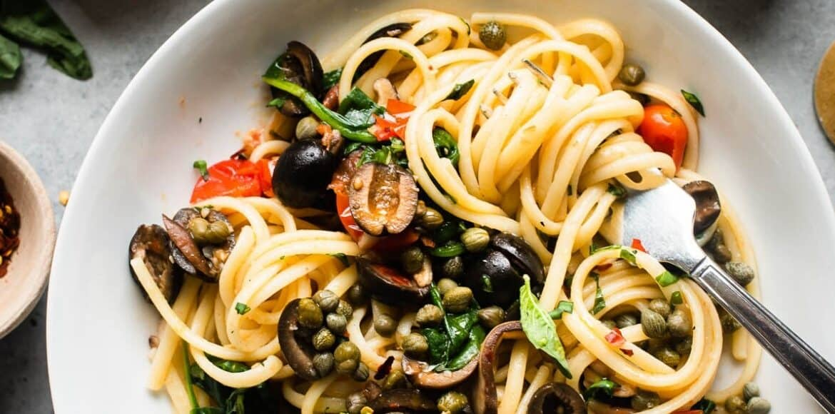 A dish with pasta, olives, and capers.