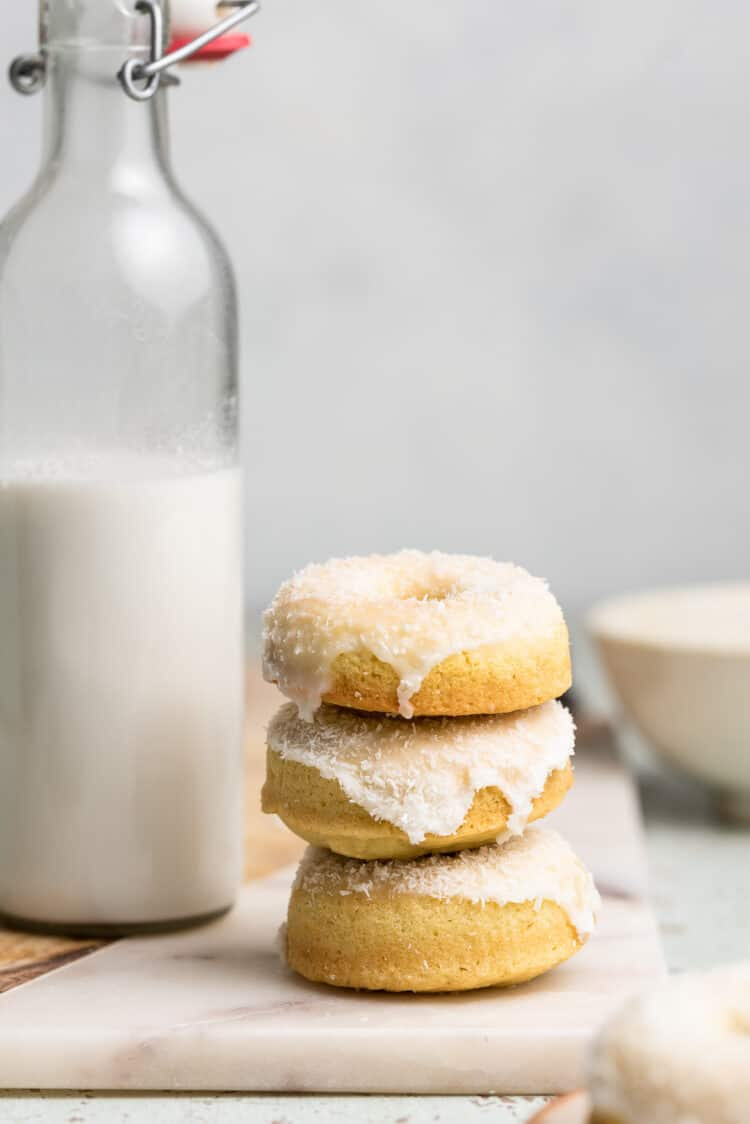 Stack of baked coconut doughnuts on a white marble board.