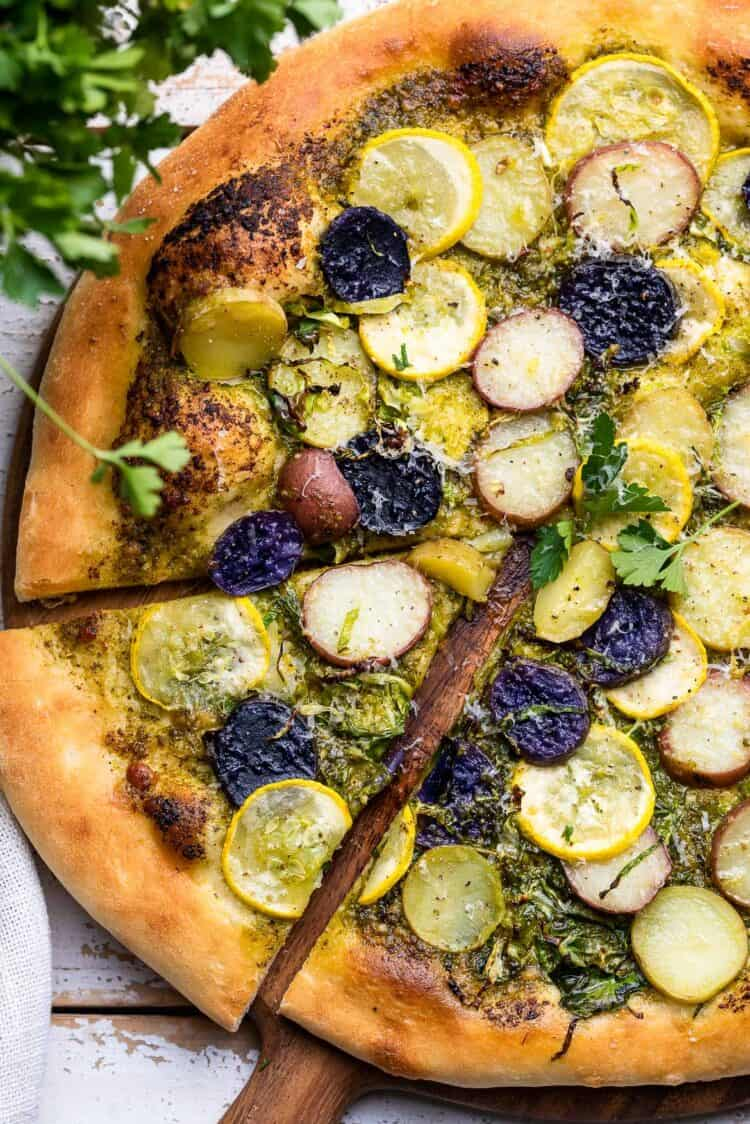 Potato Pesto Pizza with Brussels Sprouts and Yellow Squash sliced on a wood cutting board.