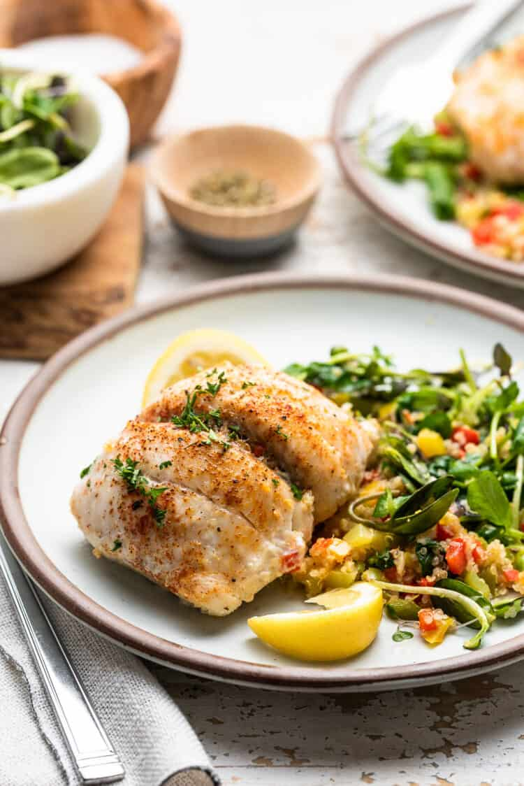 Quinoa Stuffed Sole with spinach and peppers on a white dish with greens on the side.
