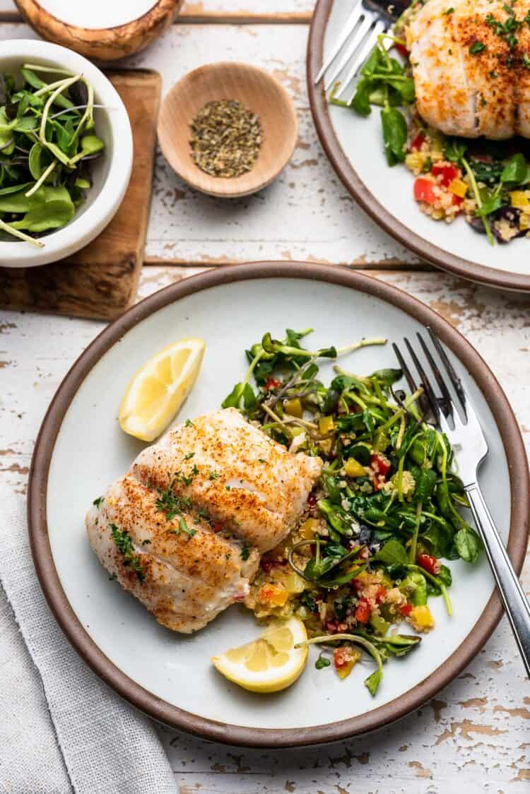 Quinoa Stuffed Alaska Sole with spinach and peppers on a white dish with greens on the side.