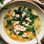 White bean soup with kale, spinach and veggies in a cream-colored bowl and croutons on the side.