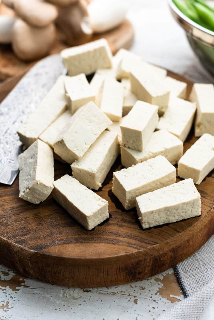 Slices of firm tofu for Filipino Crispy Tofu and Mushroom Adobo on a wooden cutting board.