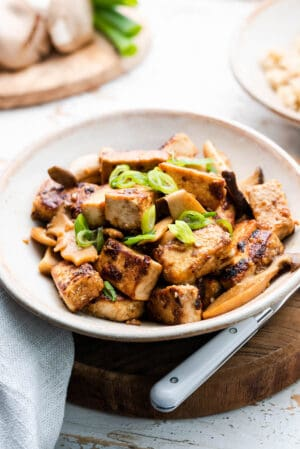 Filipino Crispy Tofu and Mushroom Adobo in a serving dish and garnished with scallions.