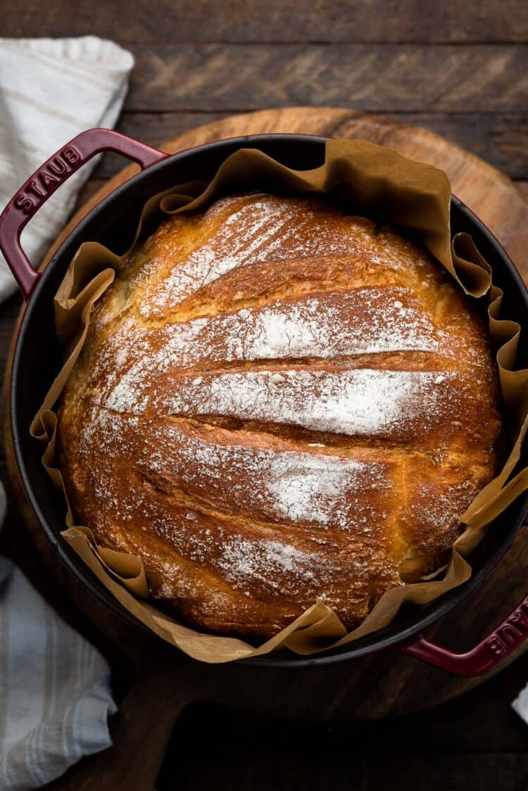 No-Knead Buttermilk Bread in a red Dutch oven lined with parchment paper.