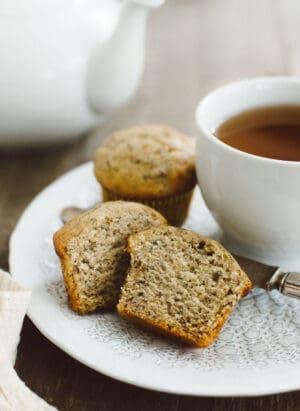A Banana Nut Ricotta Muffin halved on a plate alongside a cup of tea.