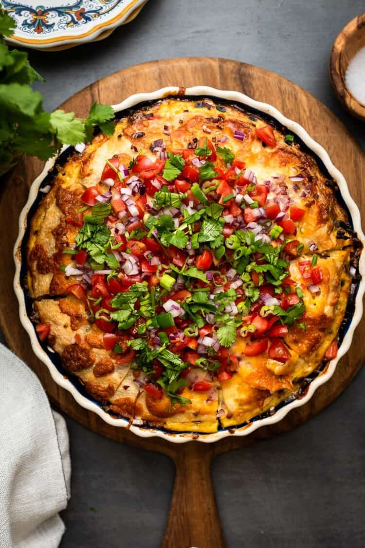 Breakfast tortilla casserole in a blue and white pie pan on a wooden board and grey table.