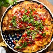 Breakfast Tortilla Pie, a tortilla casserole in a pie dish sliced, topped with onions, tomatoes, green onions and cilantro.