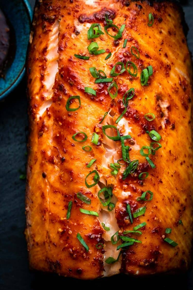 Plank Grilled Salmon with Honey Chipotle Glaze garnished with green onions.