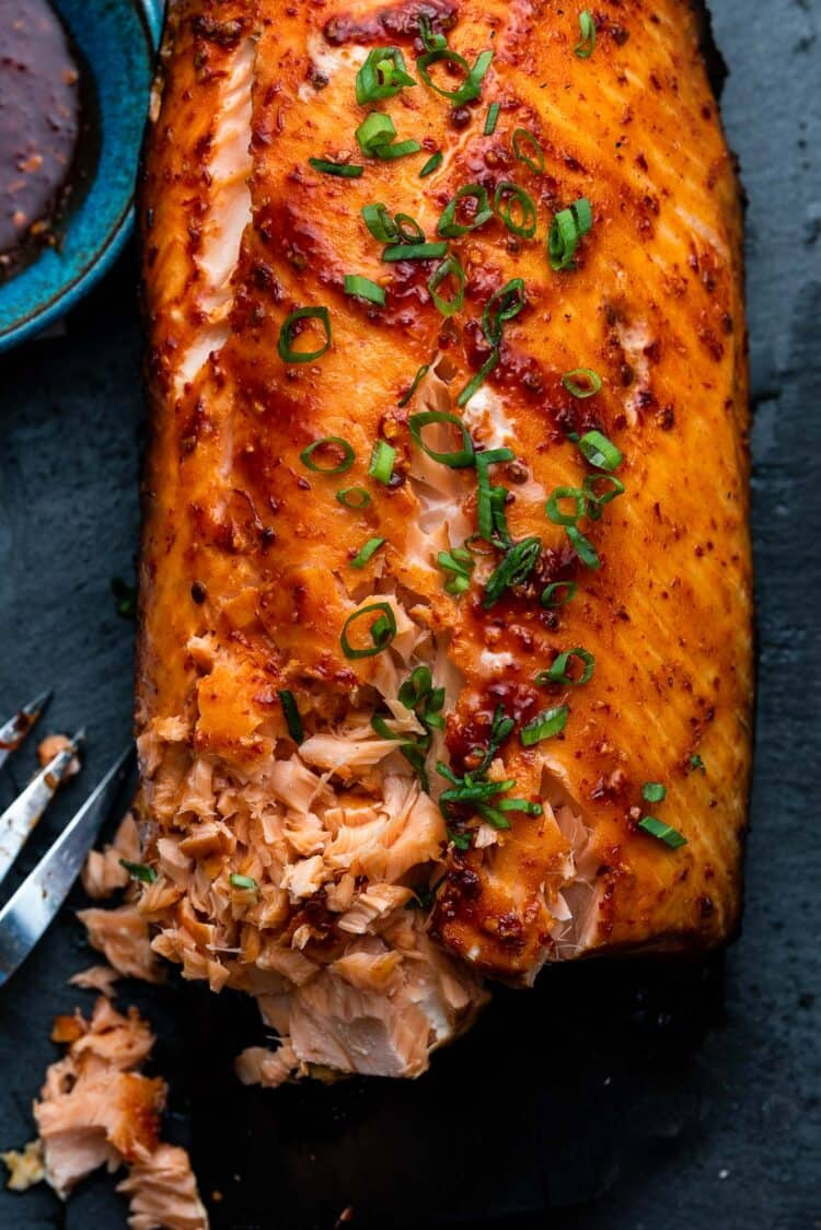 Plank Grilled Salmon with Honey Chipotle Glaze garnished with scallions.