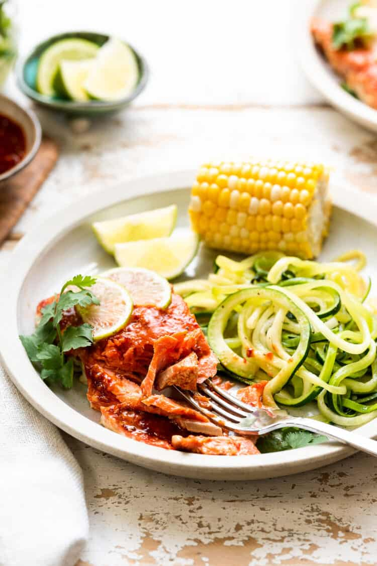 Plank Grilled Salmon with Honey Chipotle Glaze on a plate with zucchini noodles and corn.