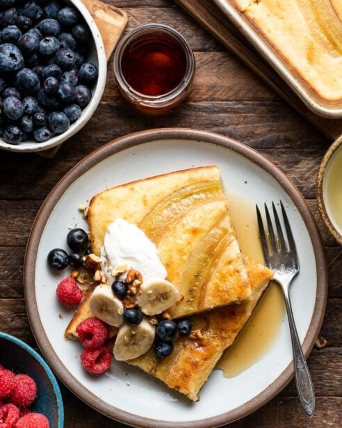 Two sheet pan banana pancakes on a white plate topped with cream, bananas, berries and maple syrup on a wooden table.