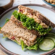 Chickpea Salad Sandwich with Feta and lettuce stacked on a plate.