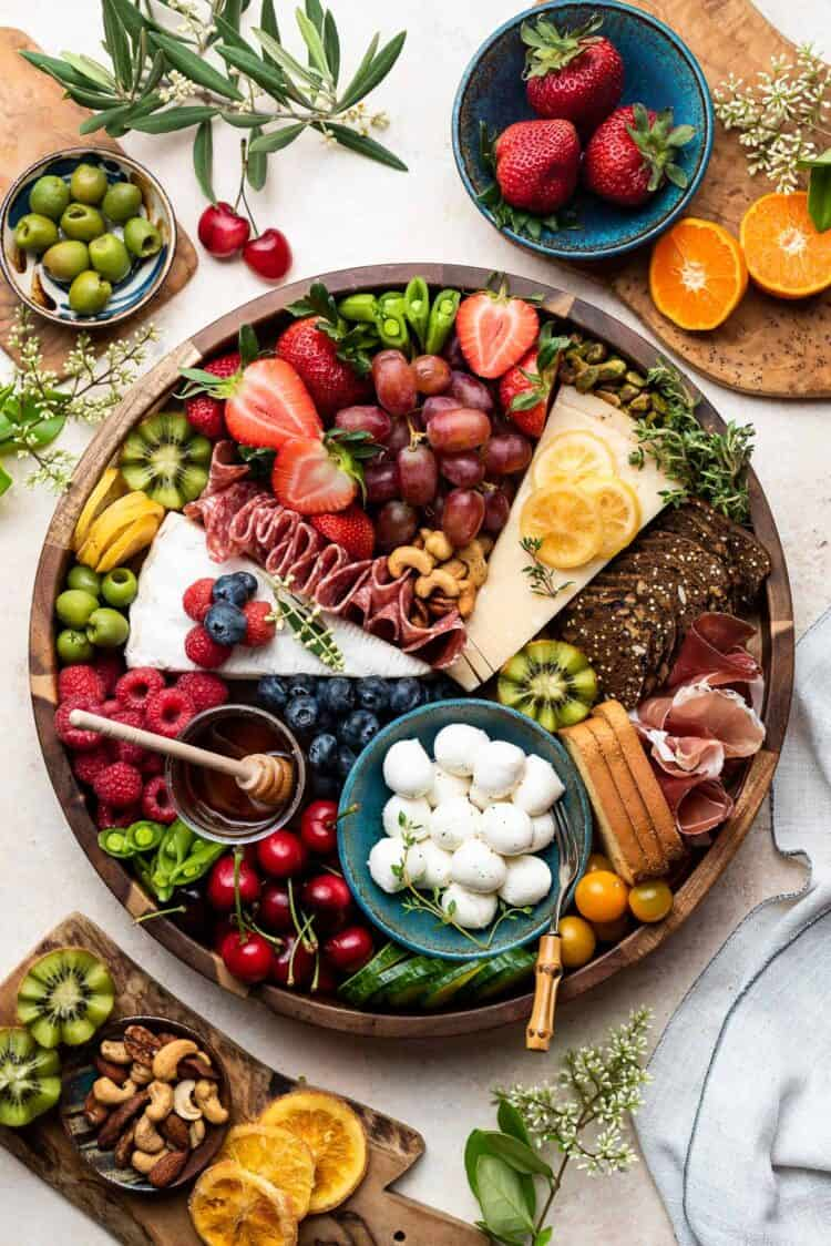 A cheese and charcuterie board with fruits, berries, vegetables and crackers in a wooden platter on a cream table surrounded by ingredients.