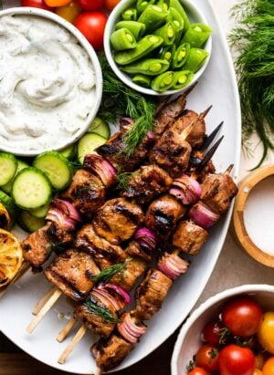 Grilled Pork Skewers made with Balsamic Marinade on a white serving platter with tzatziki and fresh vegetables.