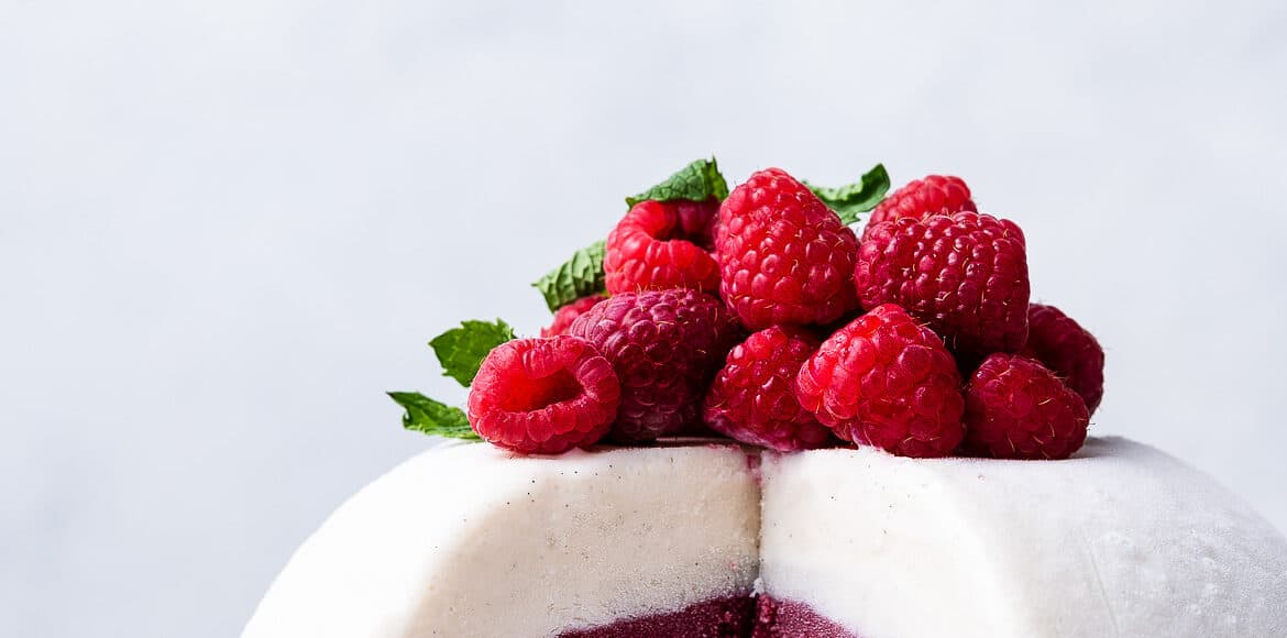 Vanilla Raspberry Ice Cream Bombe topped with fresh raspberries and mint, sliced on a white plate.