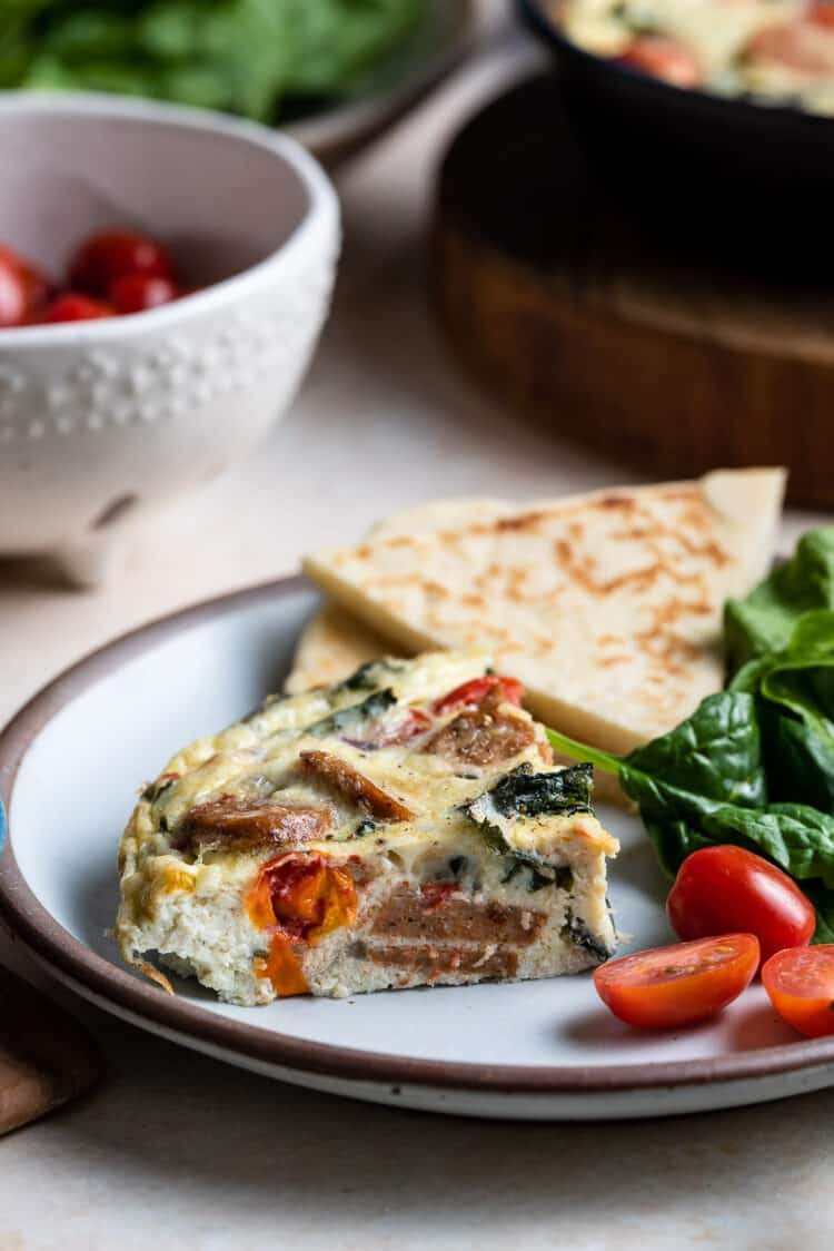 A slice of Italian Sausage and Kale Frittata on a plate.