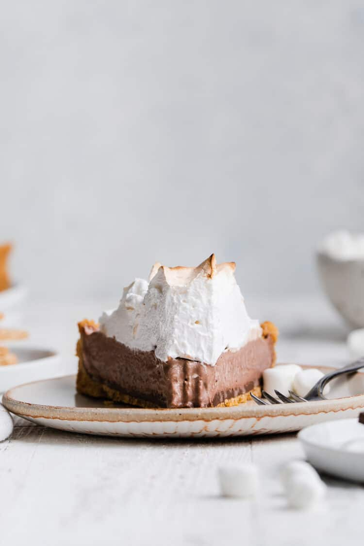 A slice of S'mores Ice Cream Pie on a cream plate.