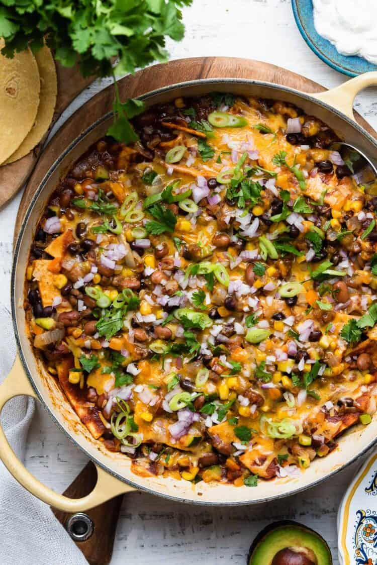 Vegetarian Enchilada casserole in a yellow skillet on a white wooden table.