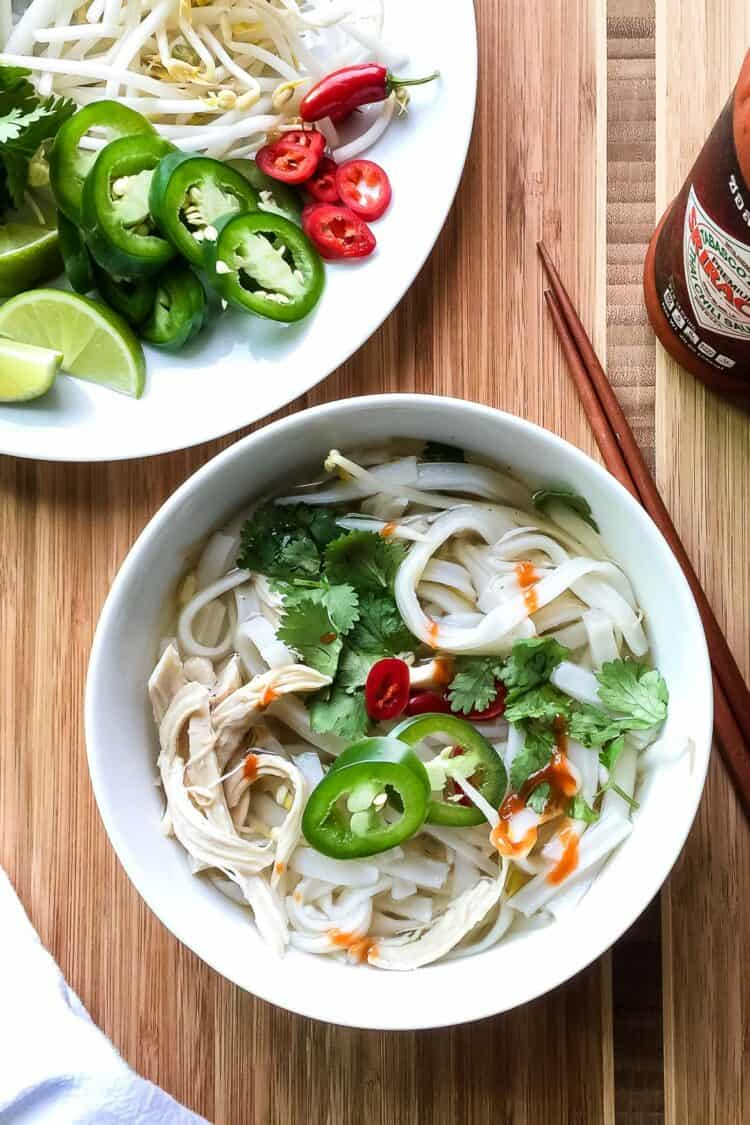 A bowl of easy thirty-minute pho made with poached chicken, fresh herbs, slices of lime, and a flavorful broth.