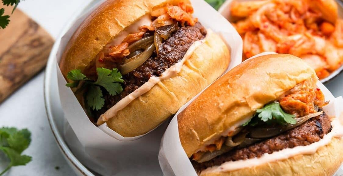 Kimchi Burgers wrapped in parchment in a bowl with a side of kimchi.