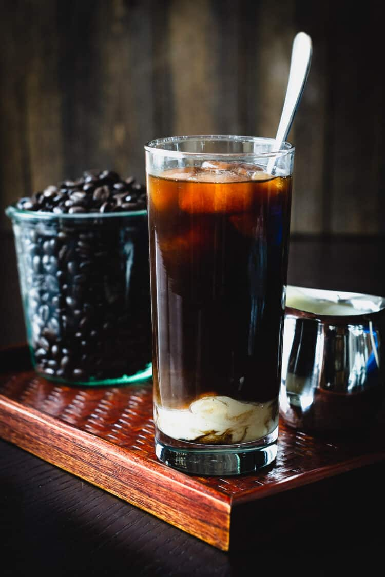 A glass of Homemade Thai Iced Coffee with coffee beans in the background.