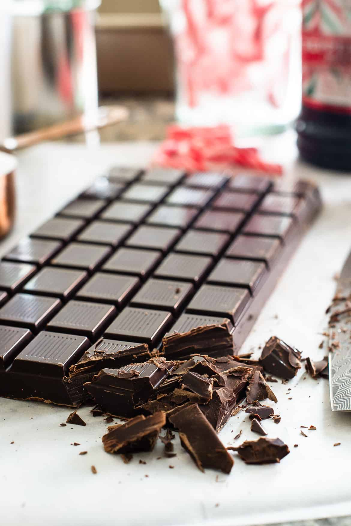 A large bar of chocolate with the corner chopped into smaller pieces.