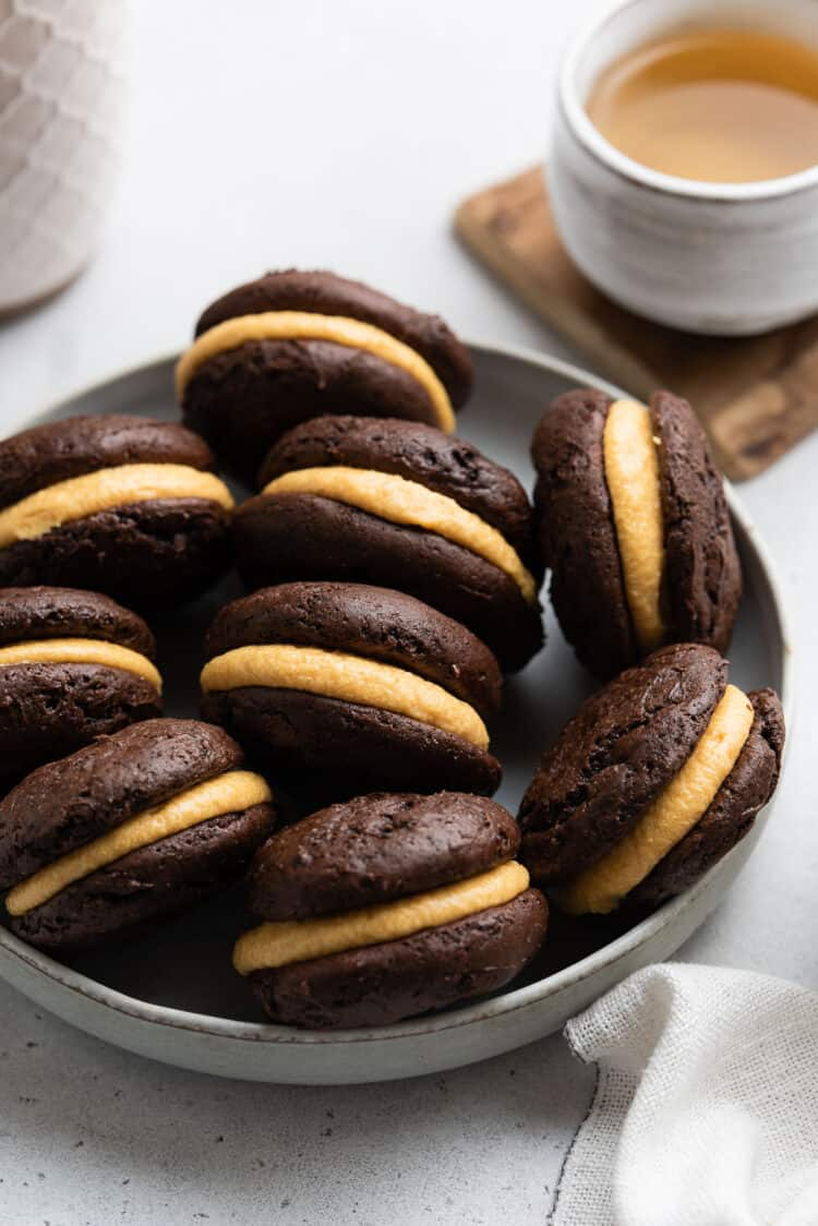 Chocolate Pumpkin Whoopie Pies in a light grey bowl with a cup of tea.