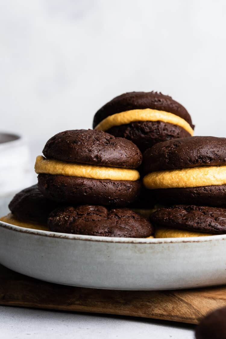 Chocolate Pumpkin Whoopie Pies stacked on a grey plate.