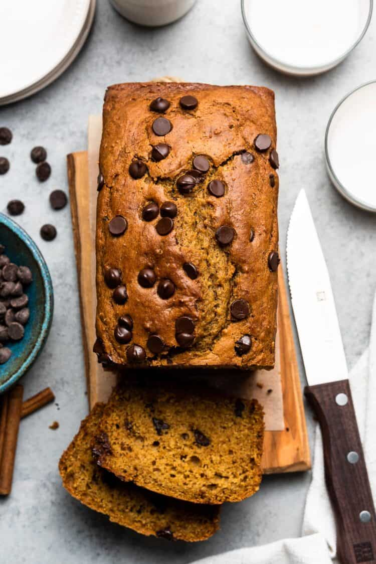 Slicing a loaf of Chocolate Chip Pumpkin Bread on a wooden board.