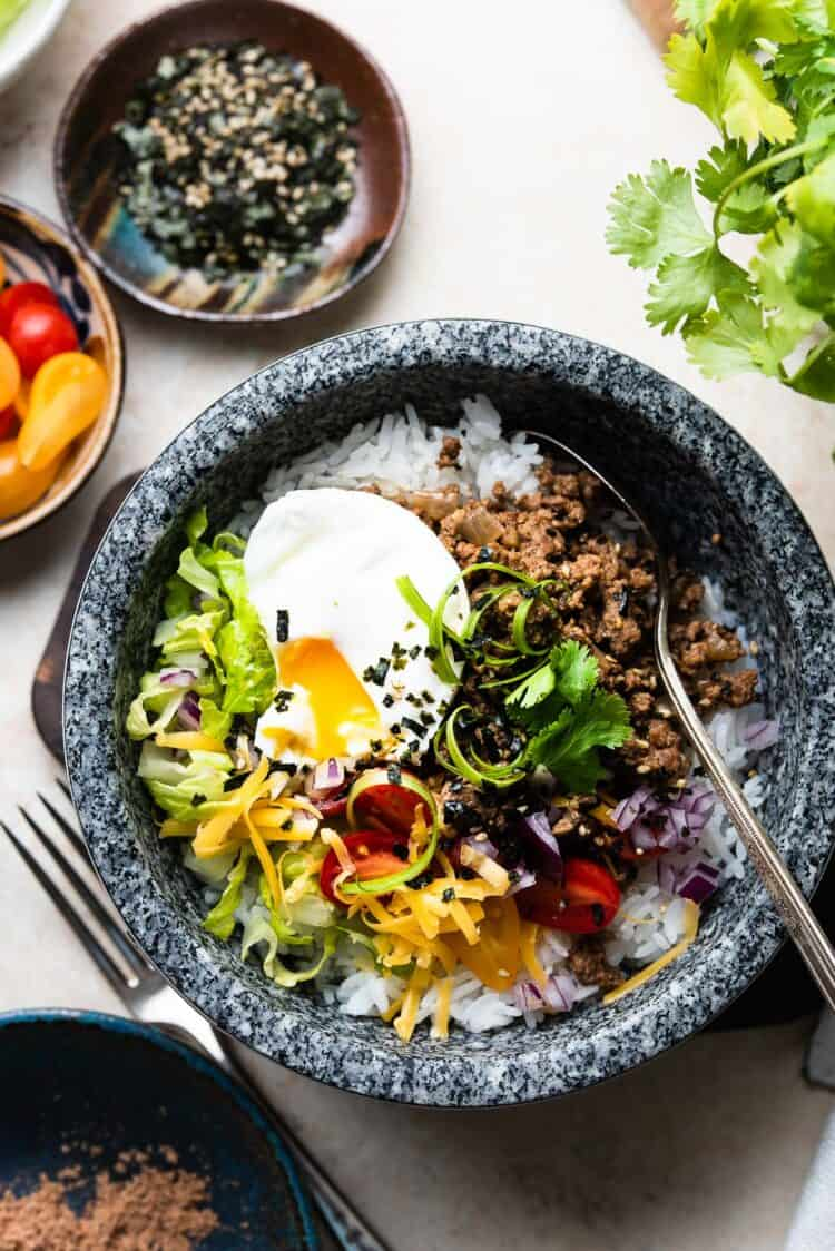 Okinawa Taco Rice in a stone bowl, topped with a poached egg.